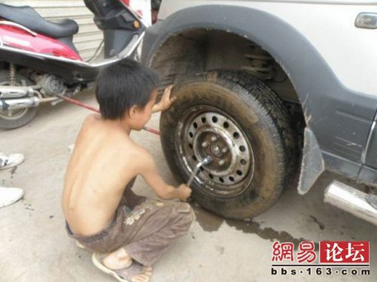 Chinese boy working as a tire repair worker